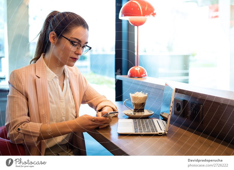Young beautiful woman with laptop , smartphone and coffee in a Restaurant Woman Notebook Telephone Mobile PDA Youth (Young adults) Businesswoman Coffee Smiling