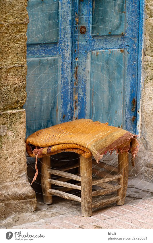 Small stool with blanket, standing in front of blue door, in the medina. Vacation & Travel Tourism Trip Sightseeing City trip Chair