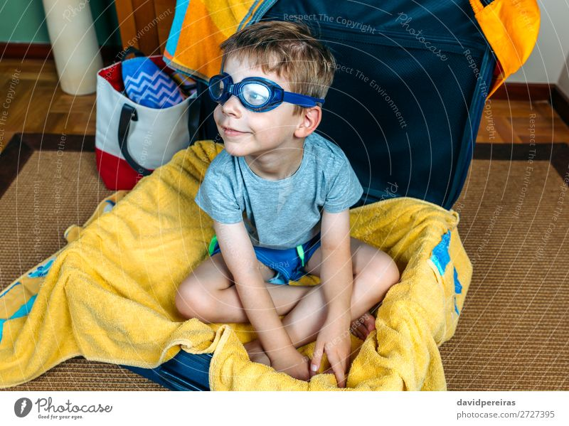 Funny boy smiling sitting inside a suitcase Lifestyle Joy Swimming pool Leisure and hobbies Vacation & Travel Trip Summer Beach Child Human being Boy (child)