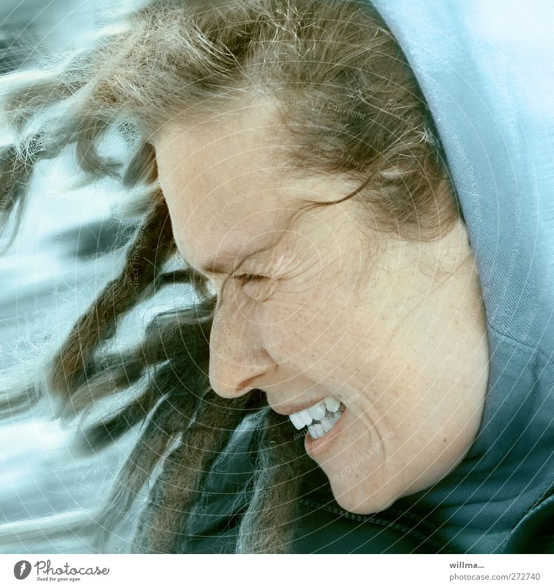 Laughing woman with dreadlocks and hood in stormy wind Young woman Youth (Young adults) Face Wind Gale Hooded (clothing) Dreadlocks Laughter Authentic Happy Joy