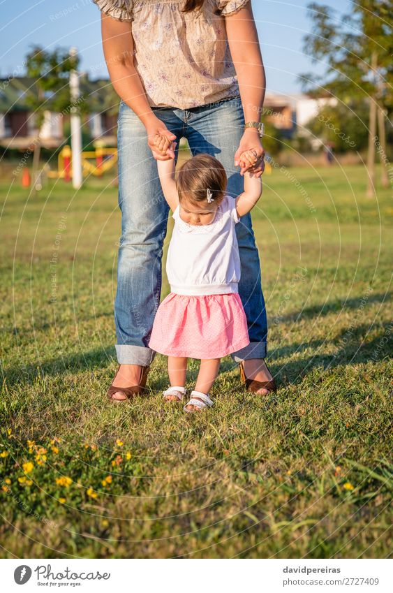 Baby girl learning to walk over a grass park Lifestyle Joy Happy Leisure and hobbies Summer Garden School Human being Toddler Woman Adults Mother