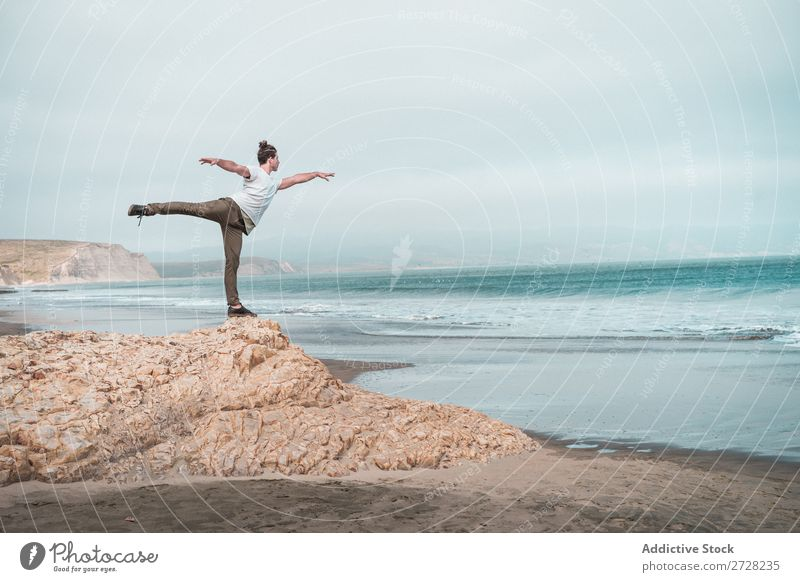 Man balancing on rock of ocean Rock Ocean Balance Calm Freedom Stand Peace Yoga Relaxation Concentrate Beach Nature Exterior shot Summer Athletic Healthy
