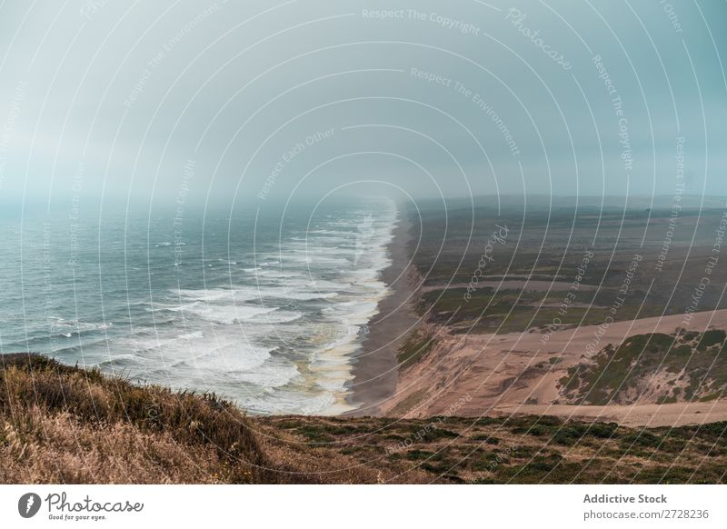 Perspective view of coastline Landscape Tide Panorama (Format) Coast Dramatic Nature Relaxation Sand Tourism Ocean Mountain Vacation & Travel Fog Exotic Summer