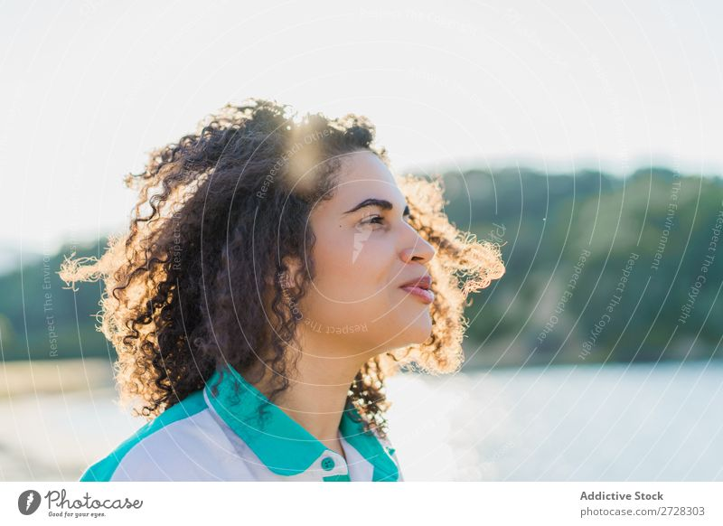Curly woman posing on nature in sunlight Woman Summer To enjoy Posture human face Landscape Nature Colour Portrait photograph tranquil Exterior shot Countries