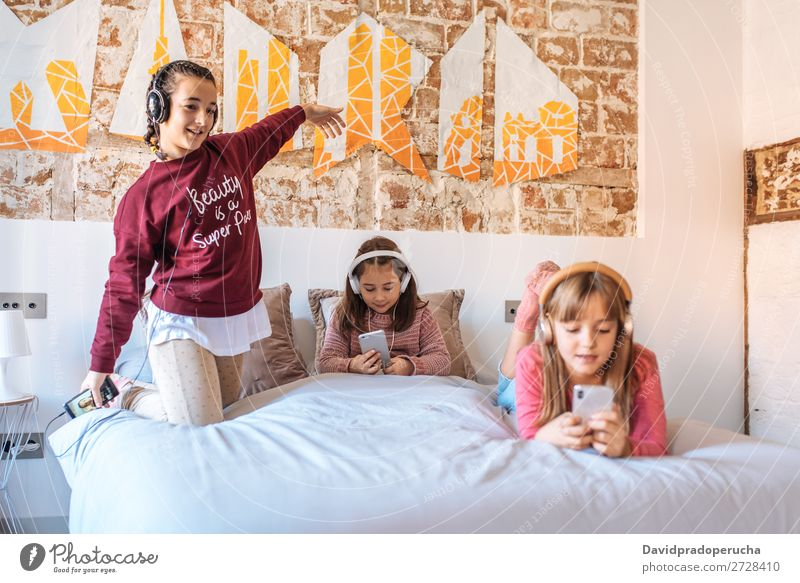 Three sisters playing with each other lying down in bed at home listening to music Bedroom Girl Happy Family & Relations White Listening Cozy Music
