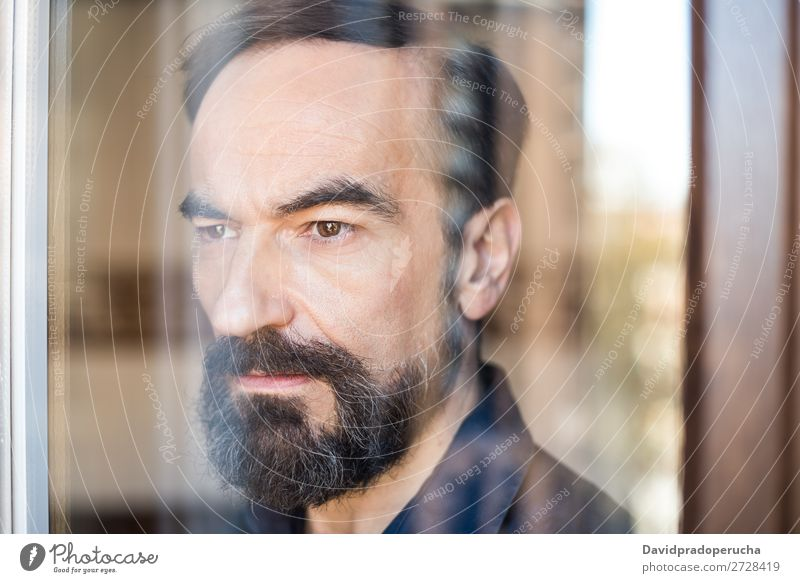 Portrait of a mature man posing thoughtful throughout the window Portrait photograph Man Mature Old Seat Beard Unshaven