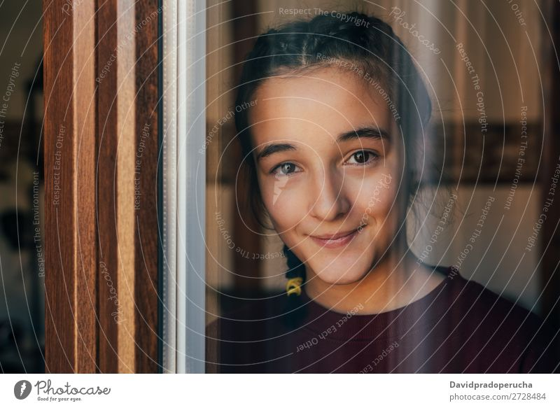Portrait of a young teenager girl standing looking throughout the window Girl Youth (Young adults) Portrait photograph Child Isolated Loneliness Face