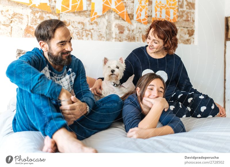 Couple relaxed at home in bed with their little daughter and the dog Affection Bed Bedroom Wife Husband Daughter Child Small Dog Pet Puppy mum dad Parents