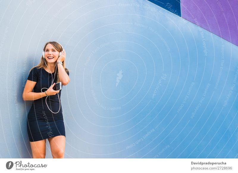 Happy young woman listening to music on the mobile phone by a colorful wall Woman Blonde Music Multicoloured Listening Telephone Wall (building) Mobile