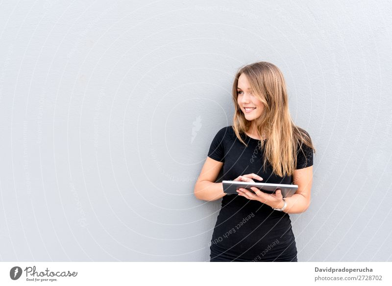 Happy young woman on the tablet by the wall Woman Isolated Blonde Tablet computer Technology Coffee Youth (Young adults) Black Dress Beauty Photography City