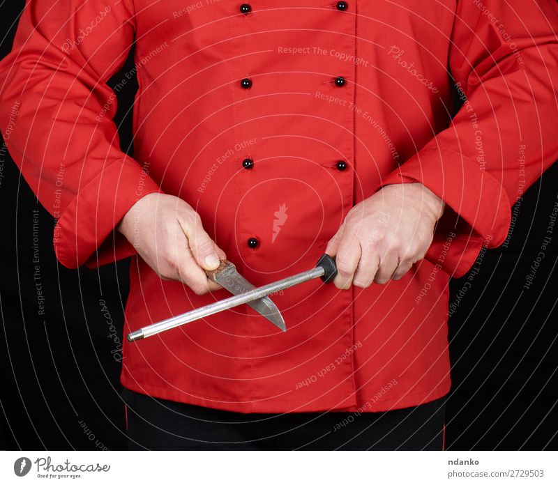 chef in red uniform sharpens a knife Knives Kitchen Restaurant Profession Cook Human being Man Adults Hand Steel Stand Red Black blade Caucasian chopping