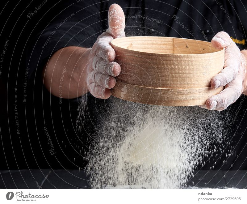man sifts white wheat flour Dough Baked goods Bread Nutrition Table Kitchen Cook Human being Man Adults Hand Sieve Wood Movement Make Fresh Black White Baking