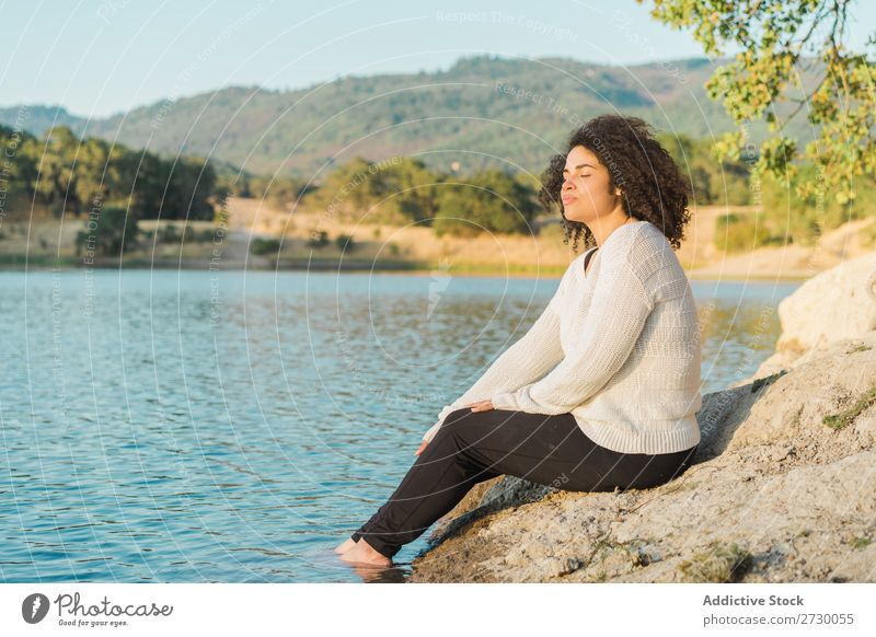 Woman resting at lake Sit Lake Coast Rest eyes closed Stone Rock Nature Water Youth (Young adults) Summer Human being Landscape Loneliness Vacation & Travel