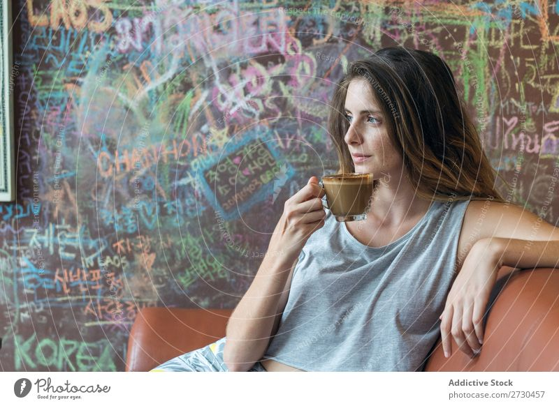 Smiling woman enjoying coffee in cafe Woman Coffee Table Café Drinking Couch Happy