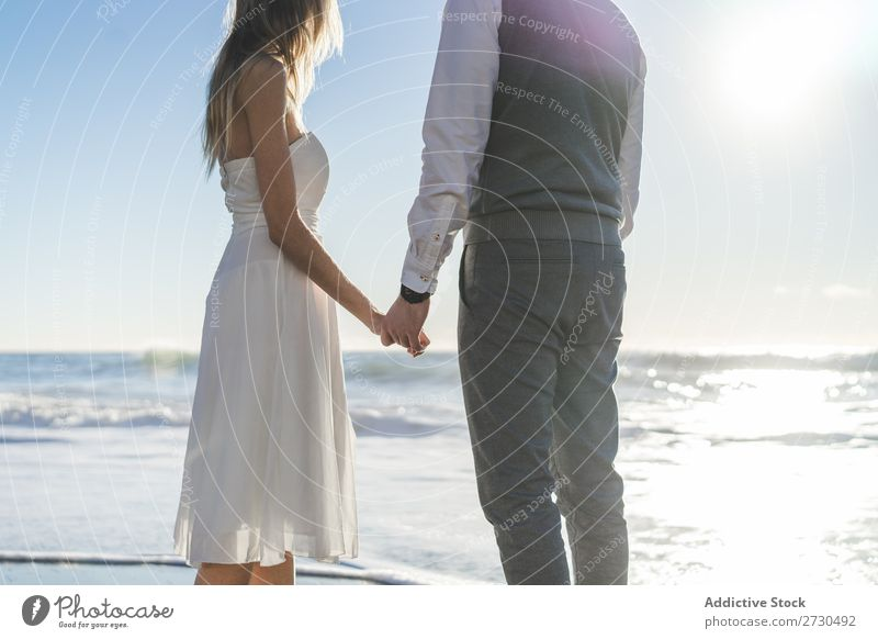 Beautiful bridal couple posing on shore Couple Beach Happiness seaside holding hands Cheerful Exterior shot Together Contentment Summer Dress Wedding