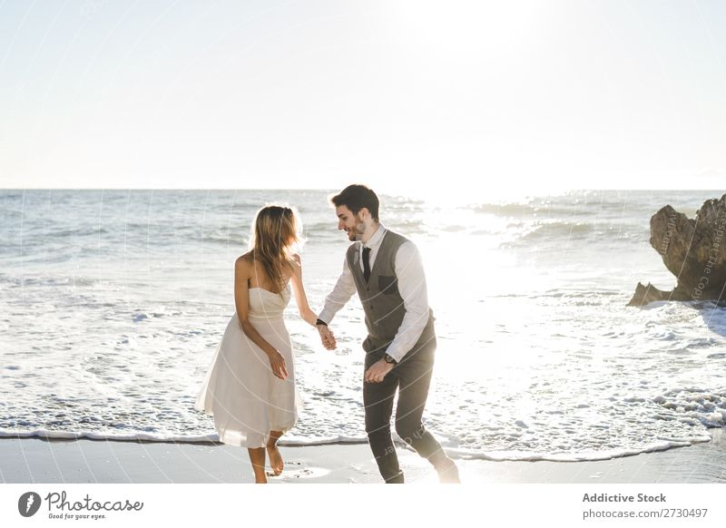 Beautiful bridal couple running on shore Couple Running Beach Happiness seaside holding hands Cheerful Exterior shot Together Contentment Summer Dress Wedding