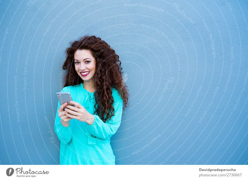 Happy young woman on the mobile phone by a colorful wall Woman Red-haired Telephone Business Businesswoman Technology Mobile Smiling Face Beauty Photography