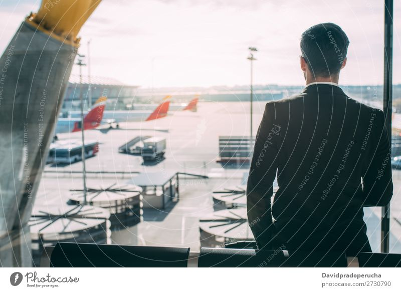 Back of a young business man standing with the suitcase at the airport waiting for the flight Airport Man Vacation & Travel Shadow Business Wait Airplane Gate
