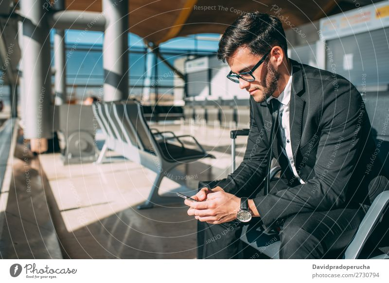 Young business man sitting on the phone with the suitcase at the airport waiting for the flight Airport Man Vacation & Travel Mobile Telephone Communication