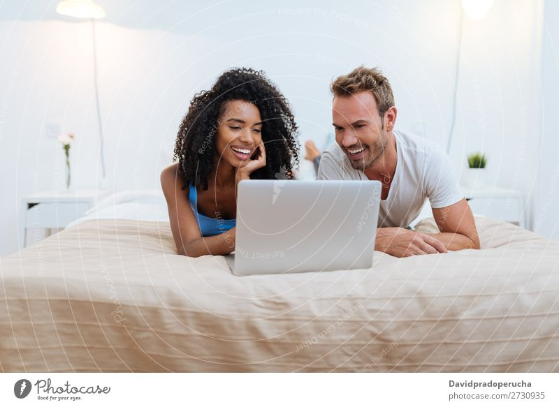 Happy young couple relaxed at home lying down in bed on the computer interracial Relationship Couple Youth (Young adults) Bed Bedroom Technology Computer