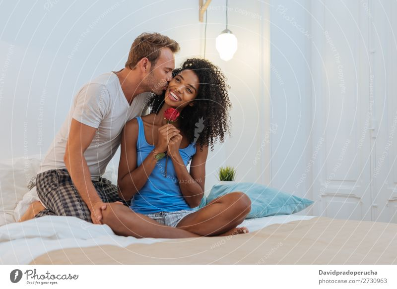 Young beautiful interracial couple in bed giving a surprise rose Affection Relationship romantic Couple Bed Bedroom Rose Red Birthday boyfriend Surprise