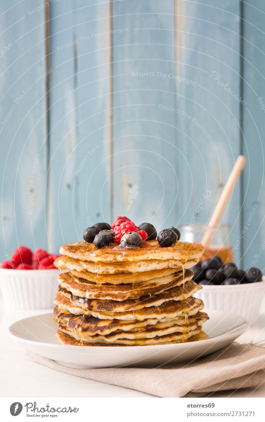 Pouring honey in pancakes with raspberries and blueberries Pancake Candy Dessert Breakfast Blueberry Raspberry Berries Red Baking Food Healthy Eating
