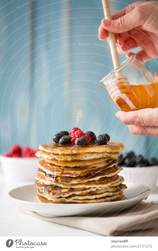 Pouring honey in pancakes with raspberries and blueberries Pancake Honey Candy Dessert Breakfast Blueberry Raspberry Berries Red Baking Food Healthy Eating