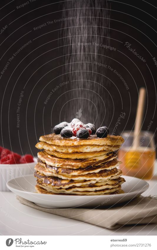 Woman pouring sugar in pancakes Pancake Blueberry Raspberry Dessert Sweet Breakfast Delicious Kitchen Decoration Plate Food Food photograph Meal Fruit Group