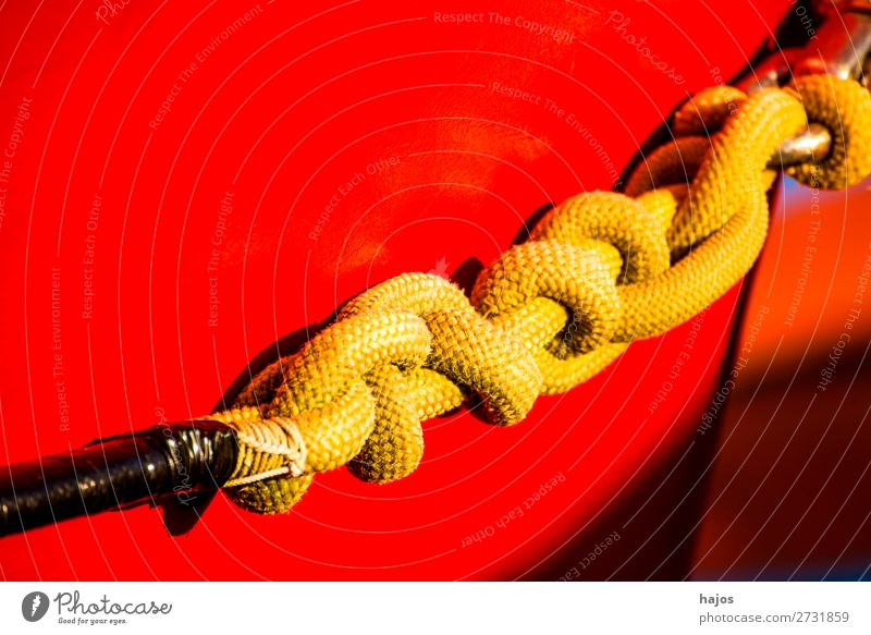 Mooring line to a red fishing cutter Design Navigation Maritime mooring rope Knot Yellow Red boat ship's side variegated colourful sunny light lashed Harbour
