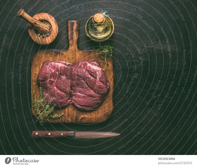 Raw marble beef meat on wooden cutting board with herbs,spices , oil and knife on dark rustic background, top view. Copy space for your design or cooking recipes