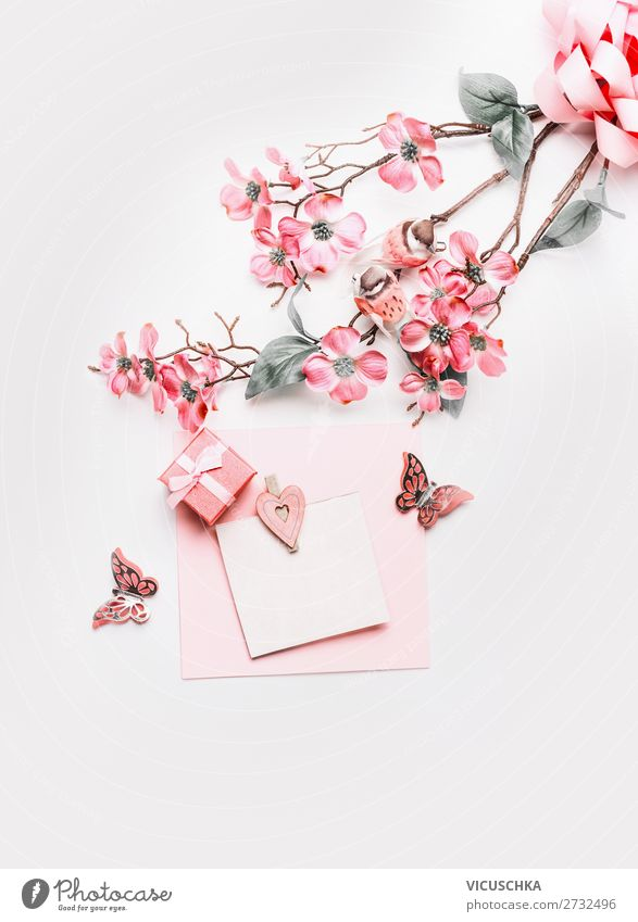 Lovely greeting card mock up with flowers, ribbon, little gift box and hearts in coral color on white background, top view. Flat lay. Abstract love and holidays concept. Blog layout