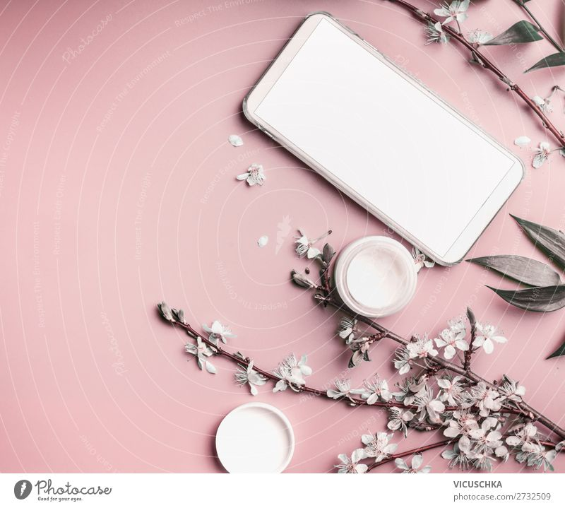 Smartphone mock up on pastel pink desktop  with cosmetic and flowers, top view. Beauty blog and female business concept smartphone background blossom branches