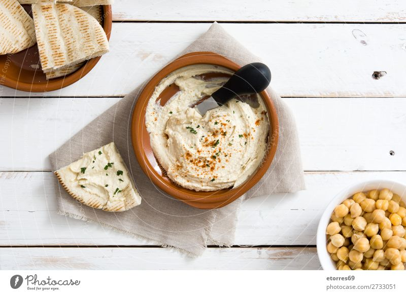Hummus in bowl and pita bread on white wooden table. Bread Food Healthy Eating Food photograph Nutrition Chickpeas Coriander Lemon Olive oil Vegan diet Arabia