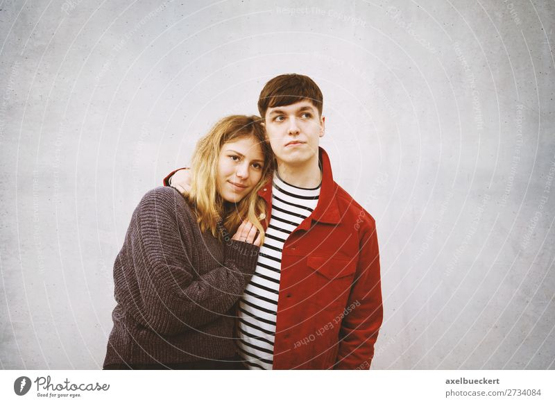 young couple stands in front of a concrete wall with free space for text Lifestyle Human being Masculine Feminine Young woman Youth (Young adults) Young man