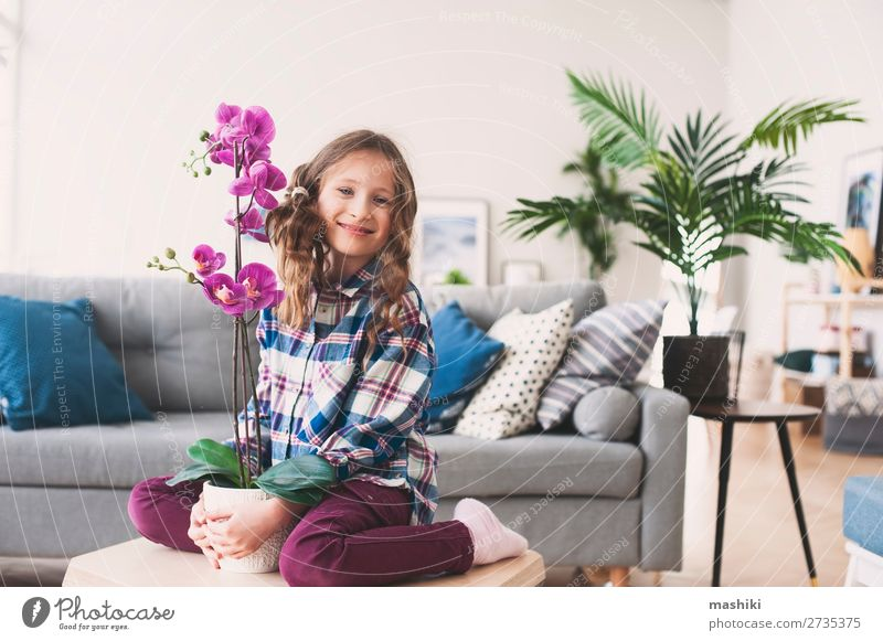 happy kid posing with orchid flower Pot Lifestyle Exotic Beautiful Flat (apartment) Living room Child Gardening Plant Flower Orchid Leaf Growth Small Modern New