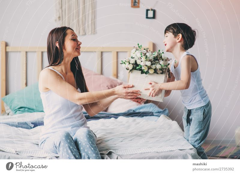 happy child boy giving flowers to mom Lifestyle Joy Happy Playing Bedroom Mother's Day Child Toddler Boy (child) Parents Adults Family & Relations Infancy