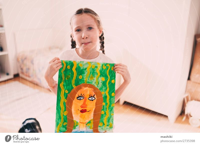 happy kid girl posing with drawing mom's portrait Lifestyle Happy Feasts & Celebrations Birthday Child Parents Adults Mother Family & Relations Infancy Art