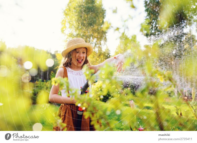 happy child girl watering flowers with hose in summer garden Lifestyle Leisure and hobbies Summer Garden Child Gardening Nature Landscape Plant Spring Flower