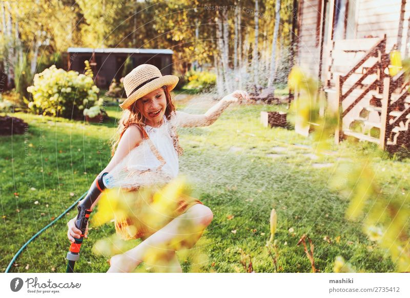 happy child girl watering flowers with hose in summer Lifestyle Joy Leisure and hobbies Playing Summer Garden Child Work and employment Gardening Nature