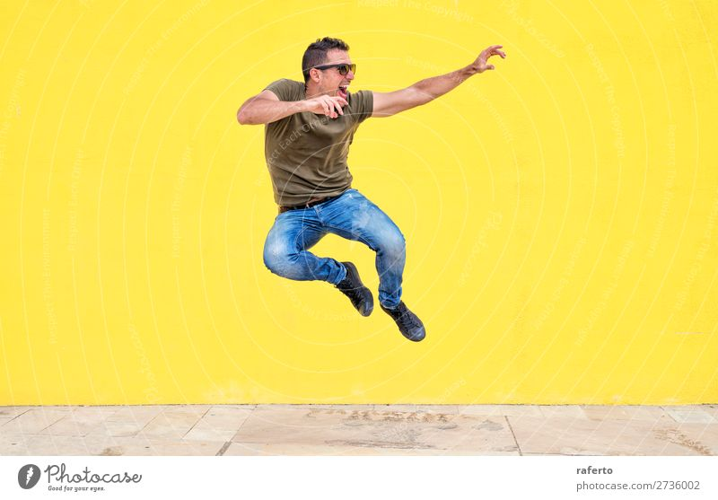 Front view of a young man wearing sunglasses jumping Human being Youth (Young adults) Man Young man White Joy 18 - 30 years Street Lifestyle Adults Yellow