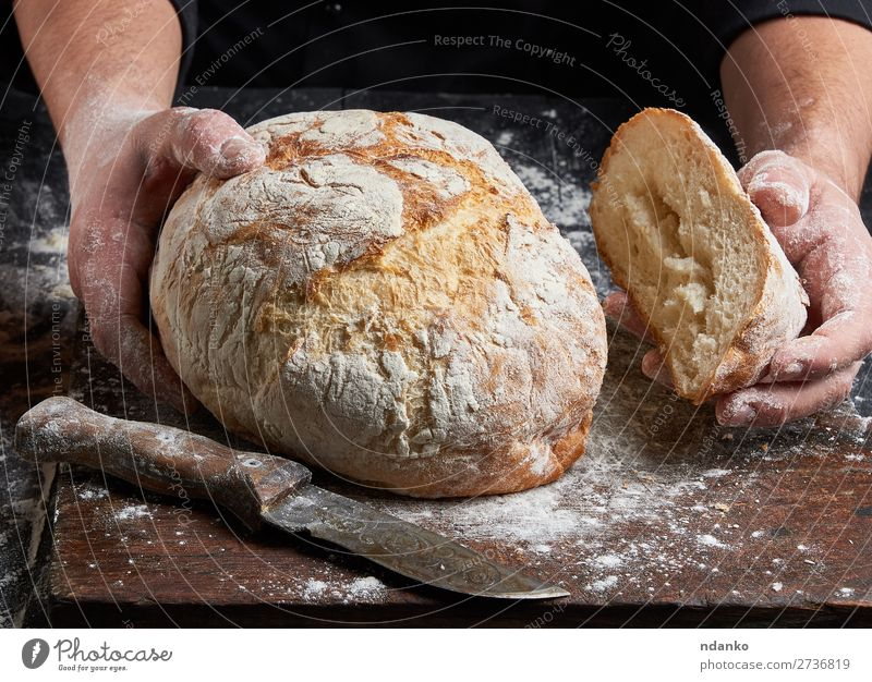 cook in a black tunic holds fresh baked bread Bread Nutrition Table Kitchen Cook Human being Hand Fingers Wood Eating Make Dark Fresh Brown Black White