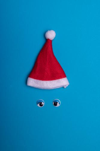 Christmas hat and wobbly eyes on blue background Joy Leisure and hobbies Playing Feasts & Celebrations Christmas & Advent Cap Paper Toys Decoration Select