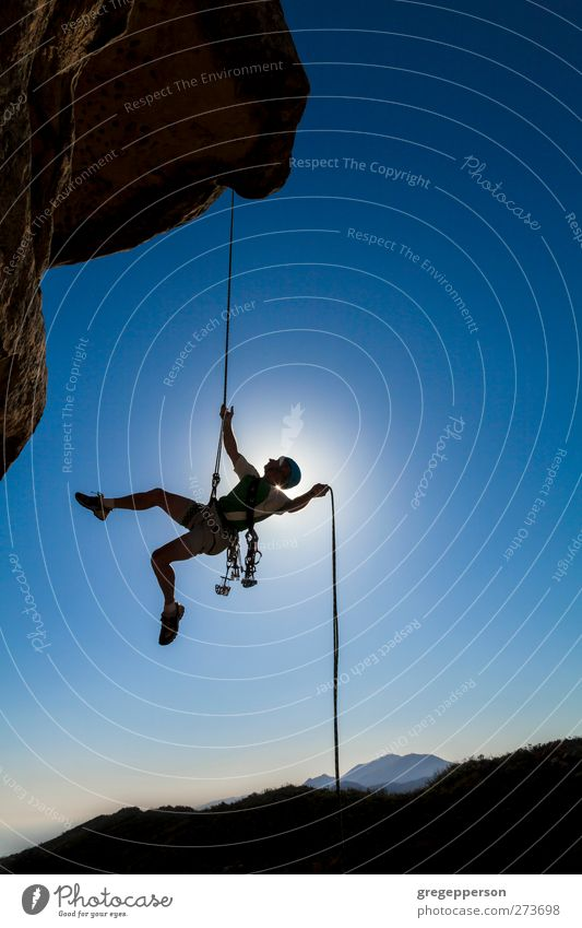 Climber on a free rappel. Fitness Life Adventure Mountain Climbing Mountaineering Rope Masculine Man Adults 1 Human being Rock Peak Hang Blue Bravery