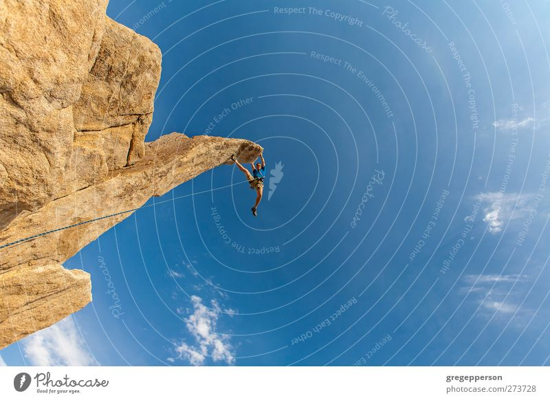 Climber dangles from the summit. Human being Blue Adults Life Rock Masculine Success Adventure Rope Peak Climbing Trust Brave Balance Fear of heights Top
