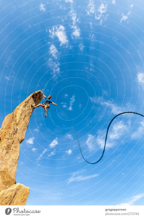 Climber dangles from the summit. Human being Man Blue Adults Life Rock Power Masculine Success Adventure Rope Uniqueness Peak Climbing Trust Brave