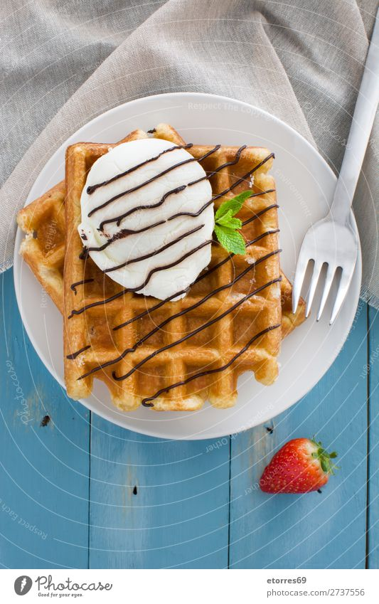 Belgian waffles with ice cream on blue wooden table Waffle Dessert Ice cream Belgium White Sweet Food background Breakfast wafer Mint Syrup Heap Strawberry