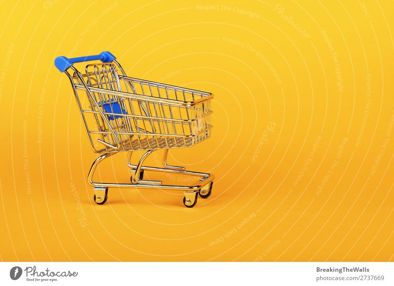 Close up retail shopping cart over yellow Shopping Economy Industry Trade Business SME Paper Toys Metal Plastic Yellow Colour Retail sector Supermarket Side
