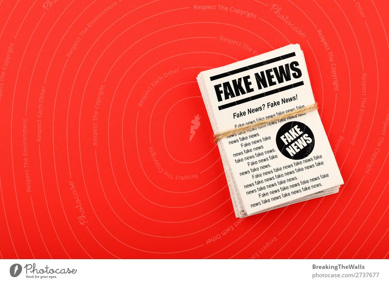 Stack of FAKE NEWS newspapers over red Colour Red Telecommunications Paper Information Media Word Newspaper Text Politics and state Conceptual design False