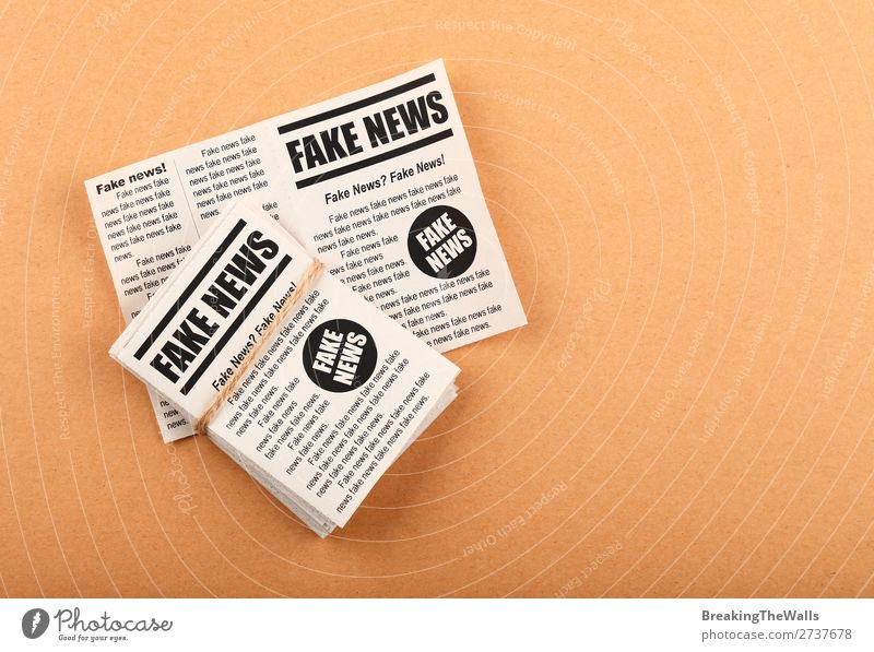 Stack of FAKE NEWS newspapers over brown paper To talk Brown Signs and labeling Paper Signage Reading Information Media Word Newspaper Text Conceptual design