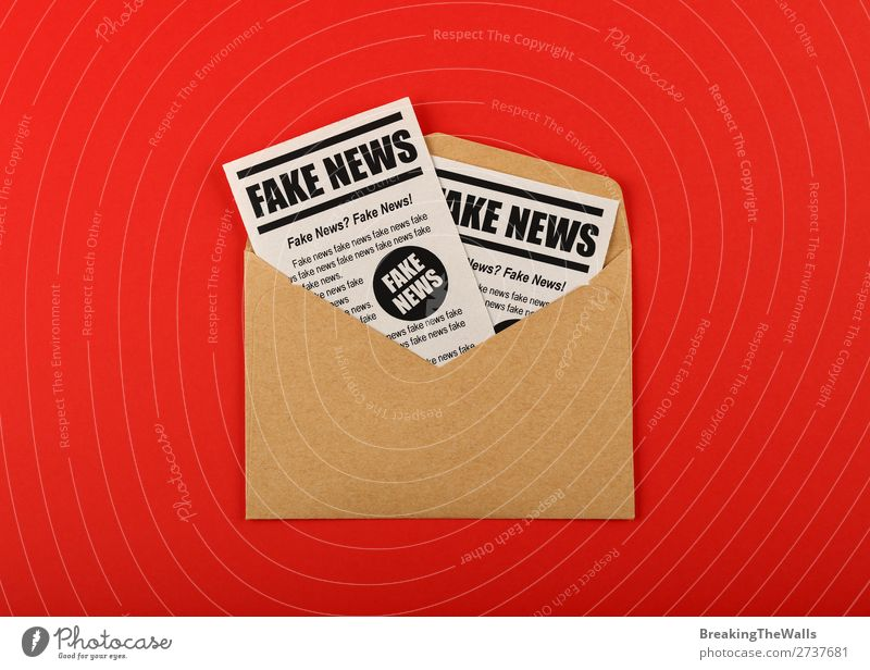 Envelope with FAKE NEWS newspapers over red Red To talk Brown Signs and labeling Paper Information Media Word Newspaper Text Conceptual design False Mail